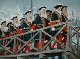 Плыть большому кораблю, далеко задумано, Бороздить его рулю, бороду Нептунову.  Долгий путь издалека, до родимой пристани, Ждать морячке моряка, на роду написано.  В океанах и морях, корабли проверятся, До костей на сквозняках, моряки проветрятся.